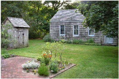 View of the 1734 smokehouse, 1822 one-room schoolhouse, and a corner of the 19th century herb garden. The late 19th century '4-holer' outhouse is located behind the schoolhouse.